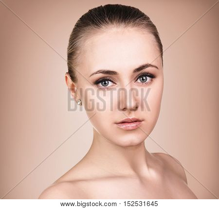 Portrait of beautiful, fresh, healthy and sensual girl over biege background