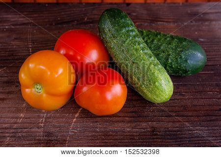 Close Up View Of Fresh, Ripe Tomatoes And Cucumbers On Wood Background