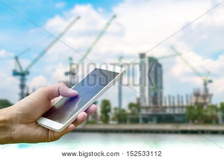 Hand holding smartphone on blurred construction site near the river and blue skycloud background