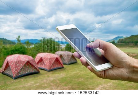 Hand holding smartphone on blurred Tent camping at Keang Kra Jan National park in Petchaburi province Thailand