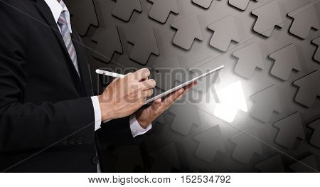 Businessman working on digital tablet, with arrow background with bright unique one, representing leader ship in business