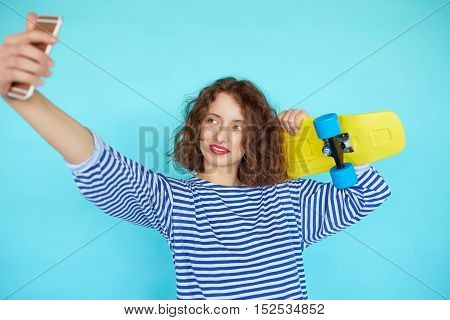 Vivid portrait of hipster pretty cool young woman with skateboard taking picture self portrait on smartphone isolated over blue background