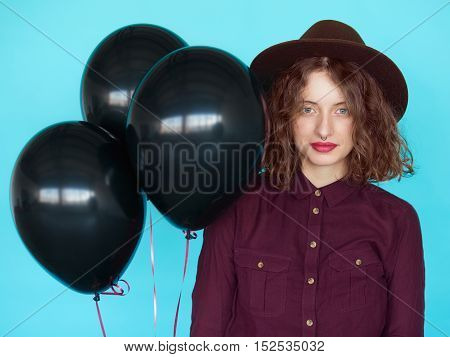 Sensual stylish young woman witn black balloons against blue turquoise background.