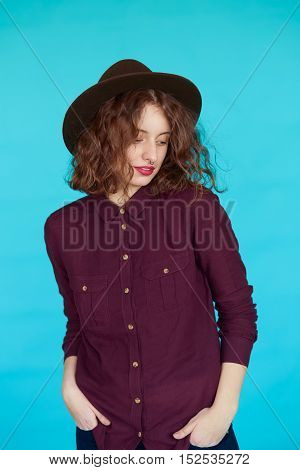 glamour portrait of a beautiful brunette in stylish hat on blue background. Vertical shot of hipster woman posing in studio, wearing dark shirt over turqoise color wall