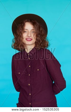 Fashion studio portrait of glamour girl, casual outfit, stylish hipster clothes hat isolated on blue turquoise color background