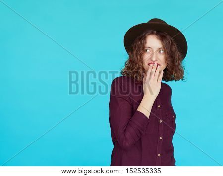 Surprised happy beautiful woman looking sideways in excitement. Fashion curly hairstyle girl wearing a hat shocked isolated on blue background with copy space.