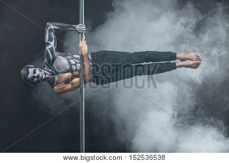 Young pole dancer with horrific body-art hangs horizontal on a pylon in the dark studio on the background of a cloud of a smoke. He holds the pylon with the hands and looks into the camera.