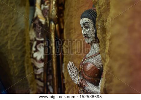 Asian figurine of a praying woman palms before her chest