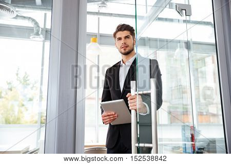 Handsome young businesman with tablet entering the door in office