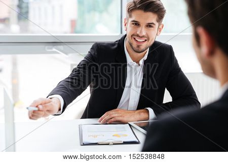 Two smiling young businessmen working on business meeting in office