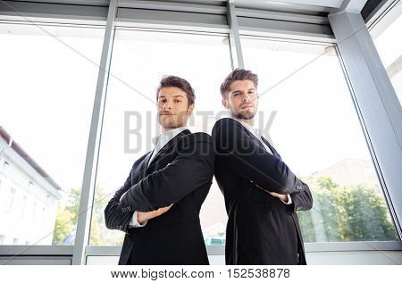 Two serious young businessmen in suit standing with arms crossed in office