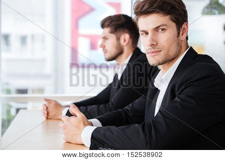 Two serious young businessmen in suit sitting in office