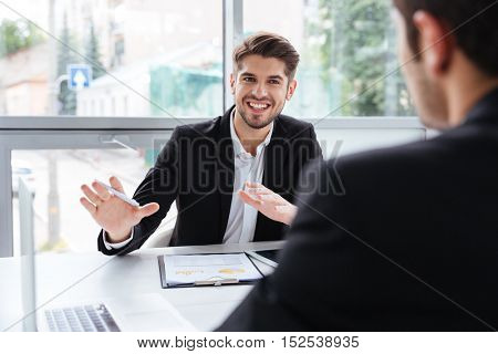 Two happy young businessmen sitting and working on business meeting in office