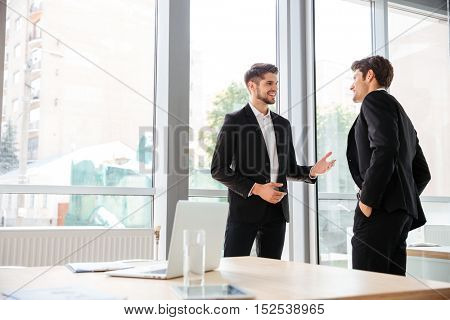 Two happy young businessmen standing and talking in office