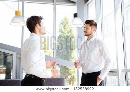 Two handsome young businessmen talking and drinking water in office