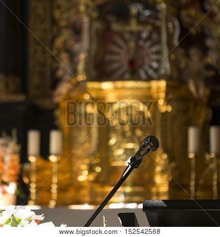 Microphone in church infront of a blurred altar.