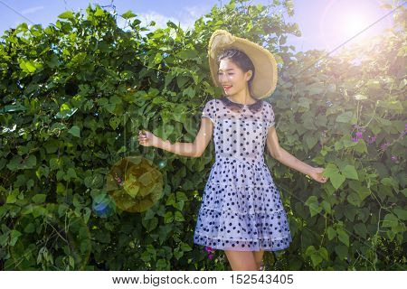 Portrait of Chinese woman by hedge in summery outfit