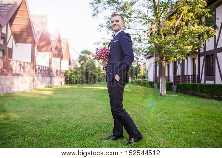Side view of smiling groom holding bouquet at lawn