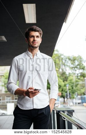 Confident young businessman standing and using mobile phone near business center