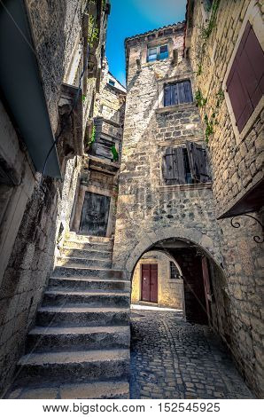 Narrow stone street of Trogir, with a scale that goes to an apartment and a stone arch