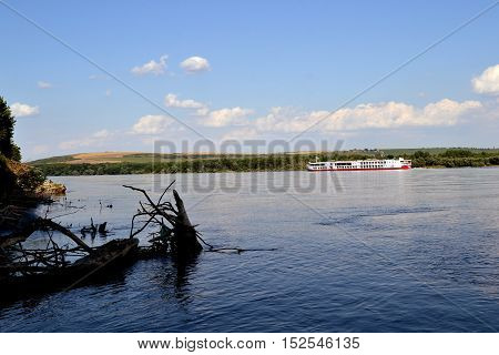 Danube beautiful day with white clouds, blue water, the roots of trees and boats.