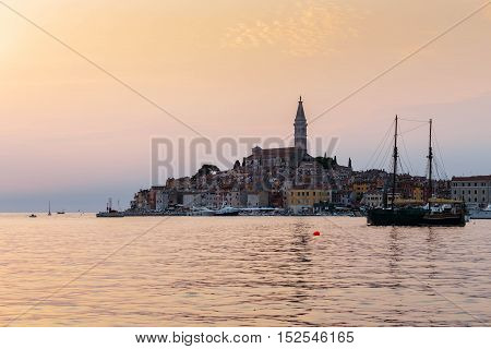 View of the historic part of Rovinj in Croatia during sunset. Above the town rises the Church of St. Euphemia. On the sea the ships.