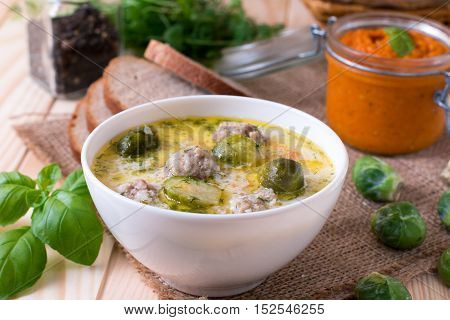 Soup with Brussels sprouts in a bowl on a wooden background