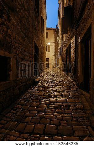 Empty evening or night european street with Cobblestones, in the light of a lantern. Rovinj, Croatia