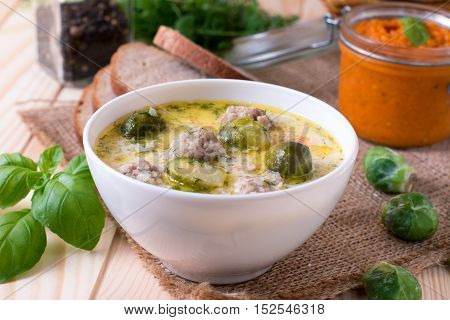 Soup with meatballs and brussels sprouts in a bowl