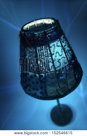 Blue candle lamp with mysterious candlelight and blue background