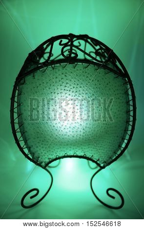 Green candle lamp with mysterious candlelight and green background