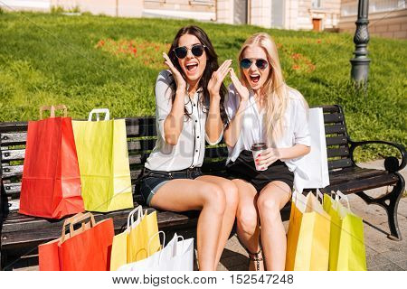 Two young excited women having fun on bench after shopping together