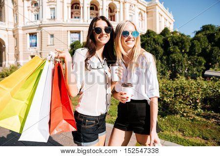 Two young fashion women with shopping bags having fun outdoors