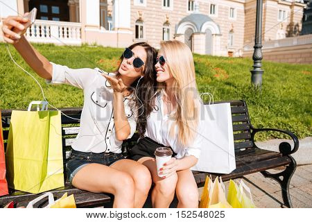 Two happy women taking selfie while resting on the bench after shopping