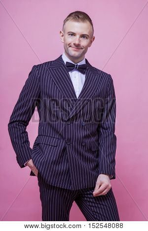 Portrait of smiling bridegroom in striped suit standing against pink background