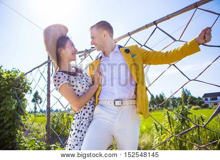Woman loving man while standing by fence at field against sky