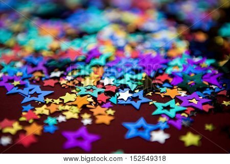 small multi-colored stars on a red background