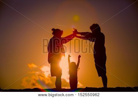 Happy family with child and pregnant mother together at sunset sky