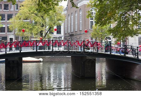 Canal and bridge decorated with red ribbon and balloons in Amsterdam