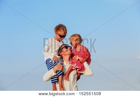 happy father with two little kids on shoulders at sky