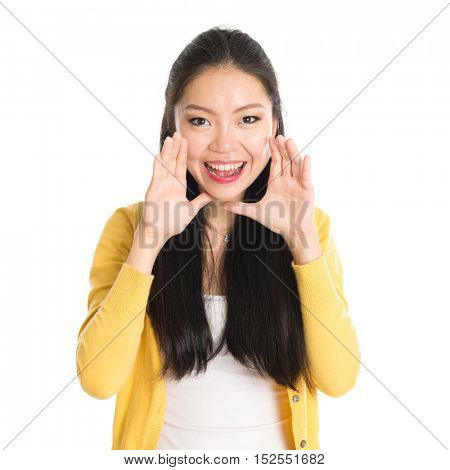Portrait of Asian female, shouting and looking at camera, standing isolated on white background.