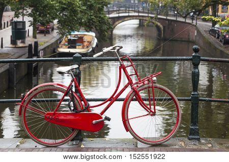 Red bike on a bridge over a canal in Amsterdam