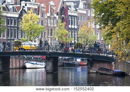 Canal and bridge with people and bicycles in Amsterdam