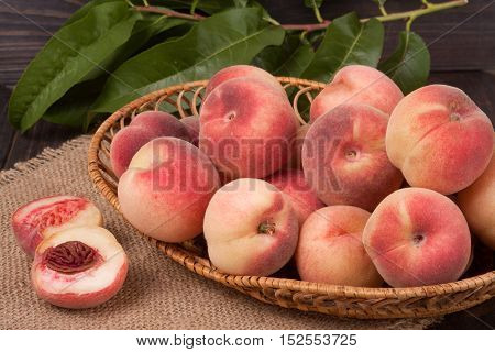 peaches in a wicker basket with leaves on wooden table.