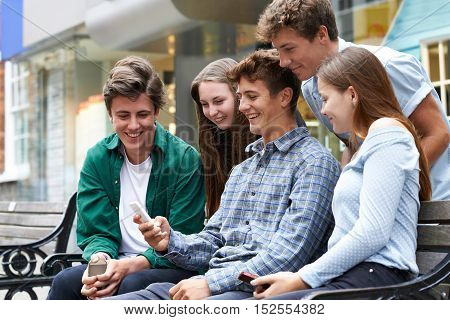 Group Of Teenage Friends Reading Text Message In Town