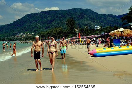 Phuket Thailand - January 9 2012: Tourists strolling along pristine Patong Beach with its white sand on the Andaman Sea
