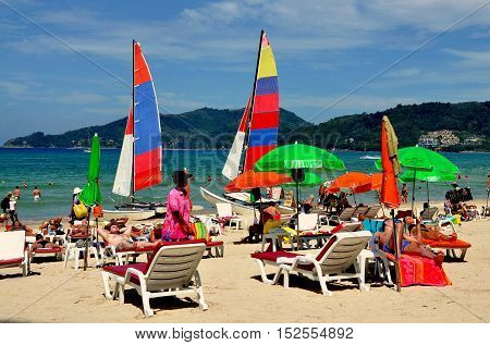 Phuket Thailand - January 11 2011: Colourful umbrellas catamarran sail boats and beach goers at Patong Beach
