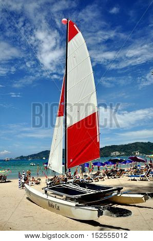 Phuket Thailand - January 11 2011: A catamaran boat with large red and white sails at Patong Beach