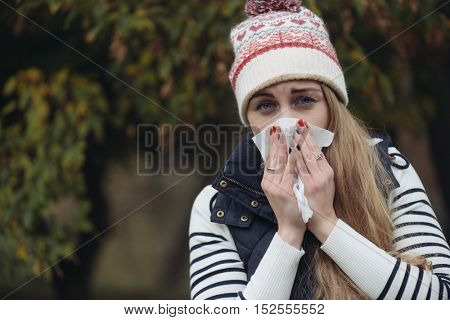 Pretty young woman blowing her nose with a tissue outdoor
