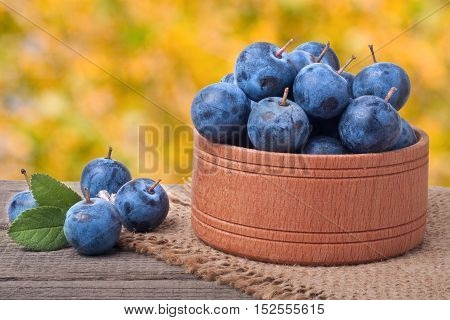 blackthorn berries in a wooden bowl on a table with sacking and a blurred background.